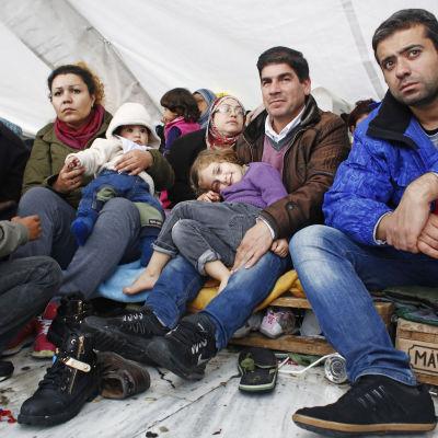 De syriska flyktingarna är nu inne på 23e dagen av sin demonstration. Grekiska frivilliga kommer med mat, filtar och regnskydd för att hjälpa. Det största problemet har varit regnet och kylan som gjort många sjuka.