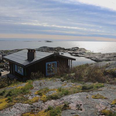 Pieni ruskea mökki sinisillä ikkunanpielillä kalliosella saarella ulkosaaristossa. Kallioiden takaa näkyy meri.