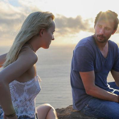 Dakota Johnson och Matthias Schoenaerts utbyter blickar sittande på en mur på italiensk ö.