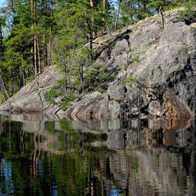 Jyrkähkö kallio nousee järvestä. Kalliolla on harvakseen pieniä lehtipuita, kallion takana on vehmaampaa metsikköä.