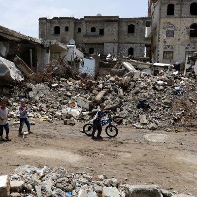 Förstörda hus och barn som promenerar bland husras. Barn promenerar i Sanaa den 3 augusti bland förstörda hus efter luftanfall från den saudiledda koalitionen