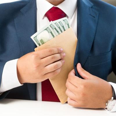 En man i kostym stoppar ett kuvert med sedlar i bröstfickan.