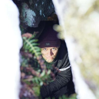 En man inne i en grotta, fotat uppifrån, från ett hål i taket på grottan.