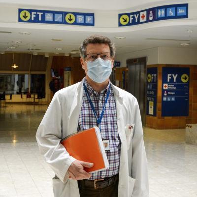 Medelålders man i munskydd och läkarrock. I bakgrunden en sjukhusaula.