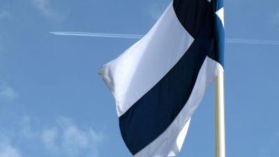 Flagga som snott sig en aning runt flaggstången. I bakgrunden ett flygplan.