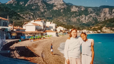 Elina och Elinas mamma på en strand i Grekland. Elinas mamma håller armen om henne och båda ser nöjda ut.