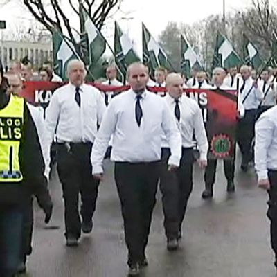 Valkopaitaisten ja mustakravattisten miesten rivistö kantaa vihreä-valkoisia lippuja. Edessä kulkee poliisi.