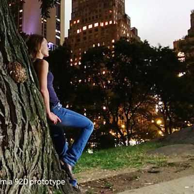 Nokian mainoskuva, jossa nainen nojaa puuhun öisessä kaupunkimaisemassa.