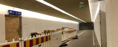 En tunnel med vita väggar och asfalterat golv. Tillfälliga staket till vänster.