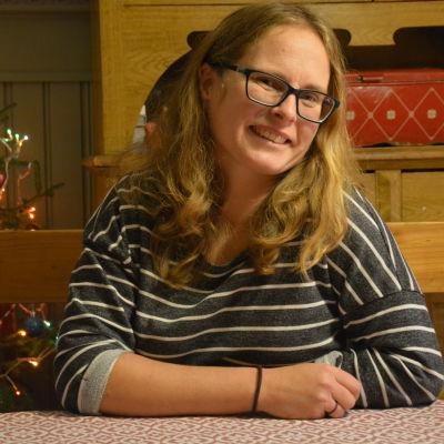 Kvinna i glasögon framför julgran.
