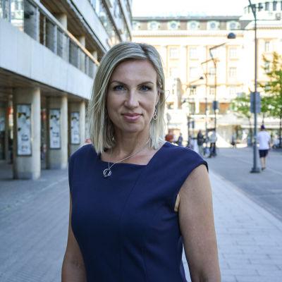 Kvinna med axellångt blont hår står och ser rakt in i kameran, i bakgrunden en gata och höghus. Det är sommar på bilden.