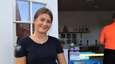 Edit Grönroos, en ung kvinna med brunt hår i hästsvans, ler mot kameran framför en glasskiosk.