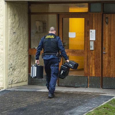 Poliisi menee kerrostaloon salkun kanssa