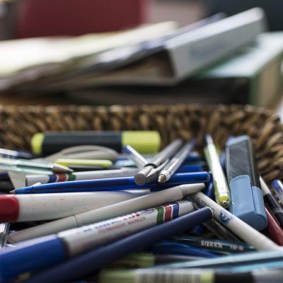 Kyniä ja mappeja toimistopöydällä.