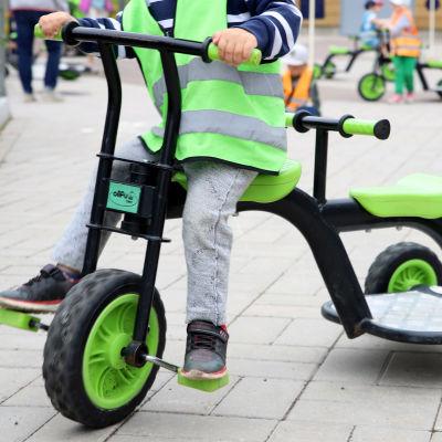 Ett barn trampar på en trehjuling.