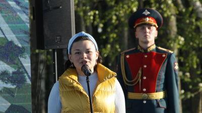 En kvinna i gul väst talar i en mikrofon. Bakom henne står en man i militär paraduniform.