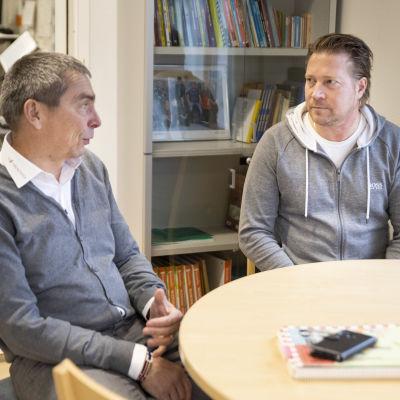 Jyrki Välimäki ja Veli-Pekka Virtanen keskustelevat pöydän ääressä.