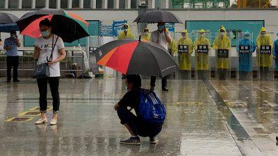 """I förgrunden några personer med paraply, och i bakgrunden en rad personer i regnrockar och utrustade med sköldar med texten """"polis""""."""