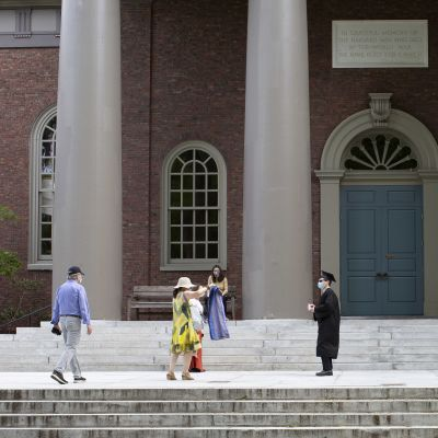 En student vid Harvard firar sin examen med sin familj under strikta coronaåtgärder, med  avstånd och ansiktskydd.