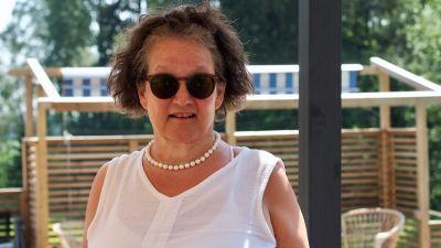 Monika Fagerholm står på en somrig terass och tittar in i kameran med solglasögon på.