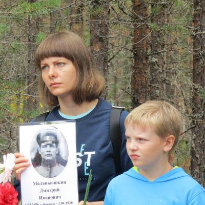 En kvinna och en pojke håller upp en bild på en soldat.