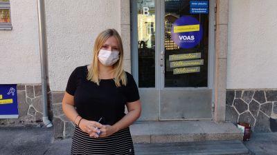 Kvinna står framför ett hus. Hon har på sig svarta kläder och munskydd.