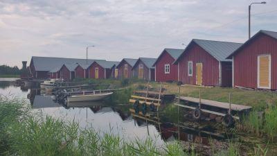Röda fiskestugor med båtar nedanför som ligger i vattnet.