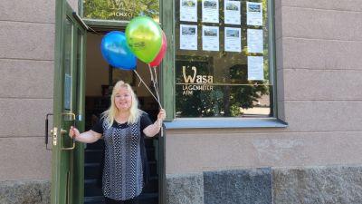 Kvinna står i dörröppning med ballonger i handen.