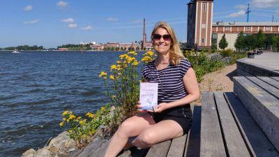 Kvinna sitter på trappa vid havet och håller i en bok. Hon ler mot kameran.
