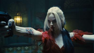 En blond kvinna i röd klänning och näsblod står med pistoler utsträckta i båda händerna.
