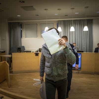 Rahanpesusta syytetty peittää kasvonsa oikeudenkäynnin alkaessa.