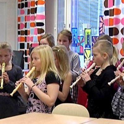 Kuvassa nokkahuilua soittavia koululaisia uudessa luokassa.