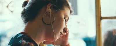Kvinna som sitter och lyssnar på något.