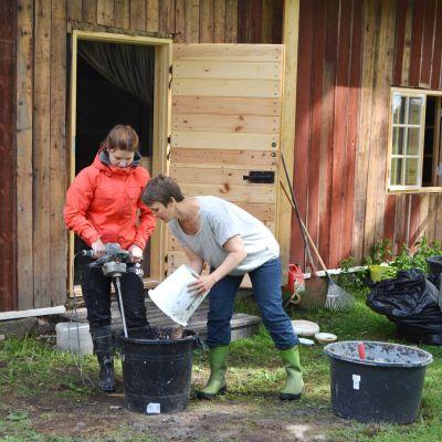 Ingrid Henriksson och Eva Godenhielm-Vuori blandar ihop massan för lerklining ute på gården.