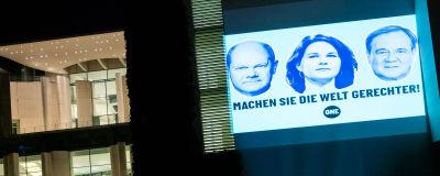 """Tysk valreklam på en byggnad där det står """"Kan du göra världen mer rättvis?""""."""