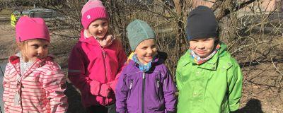 Fyra dagisbarn kisar mot solen i färgglada ytterkläder.