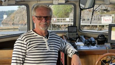 En man står inne i hytten på en båt.