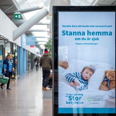 THL:s stora skylt som säger att man ska hållas hemma om man är sjuk. Bilden är tagen i ett köpcentrum i mars 2020