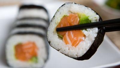 En bit rullad maki-sushi mellan två matpinnar med flera sushibitar i bakgrunden.