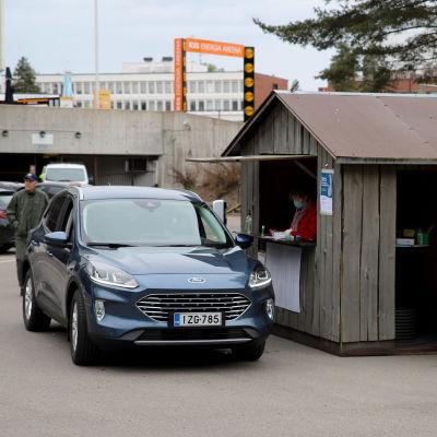 henkilöauto on pysähtynyt vaalivirkailijoiden kojun kohdalle Kouvolan drive-in-äänestyspaikalla jäähallin pihassa.
