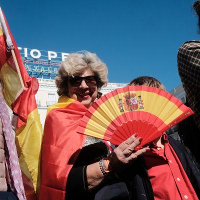 Nainen kädessään Espanjan lipun värejä toistava viuhka.