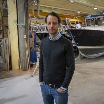 Man poserar framför båt i industrihall.