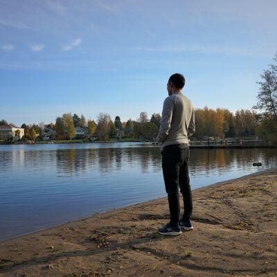 Ung man står vid vattnet.