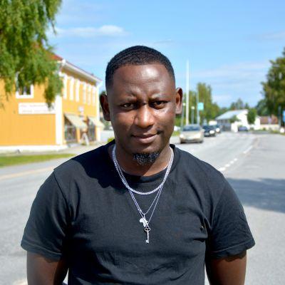 Man i svart t-skjorta tittar mot kameran. I bakgrunden syns en gata.
