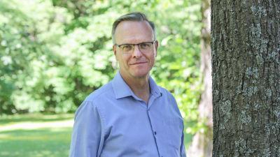 Arkkipiispa Tapio Luoma lähikuvassa kesäisessä maisemassa puun varjossa.