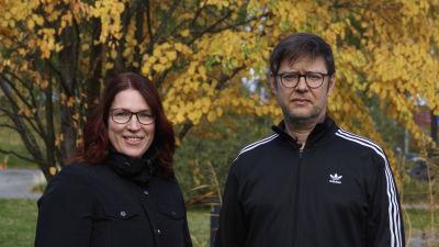 En man och en kvinna fotograferas med gula lövträd i bakgrunden.