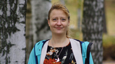 Kvinna i turkos jacka ler mot kameran. Hon har ett smycke som föreställer en svala.