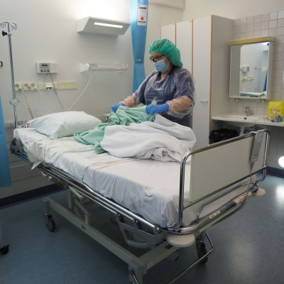En sjukskötare byter sängkläder på en sjukhussäng.