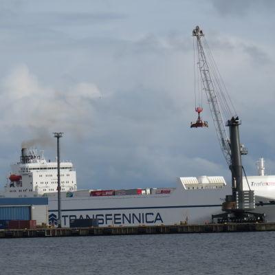 Ett fartyg lastas i en hamn.