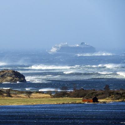 En bild på ett kryssningsfartyg i kraftig storm. I förgrunden syns land och hav.